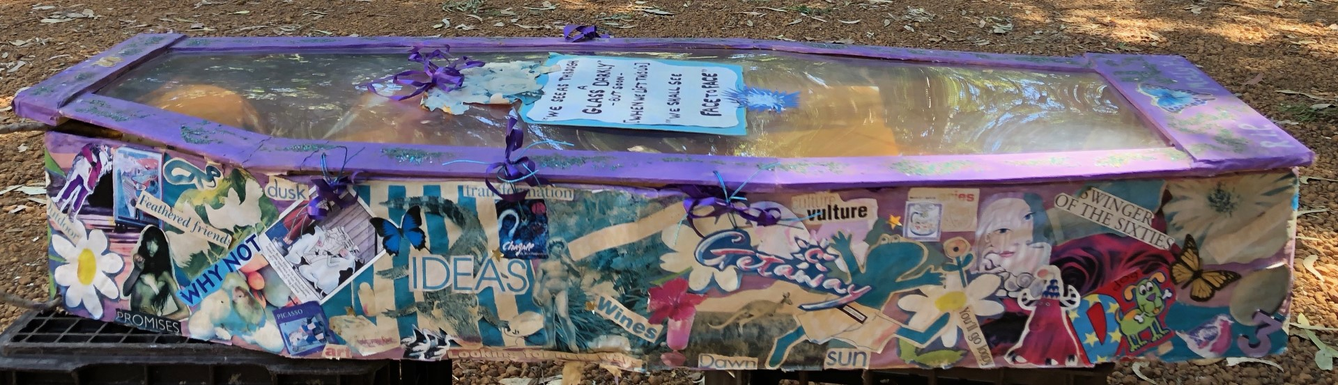 Colorful coffin with collage and a glass lid.